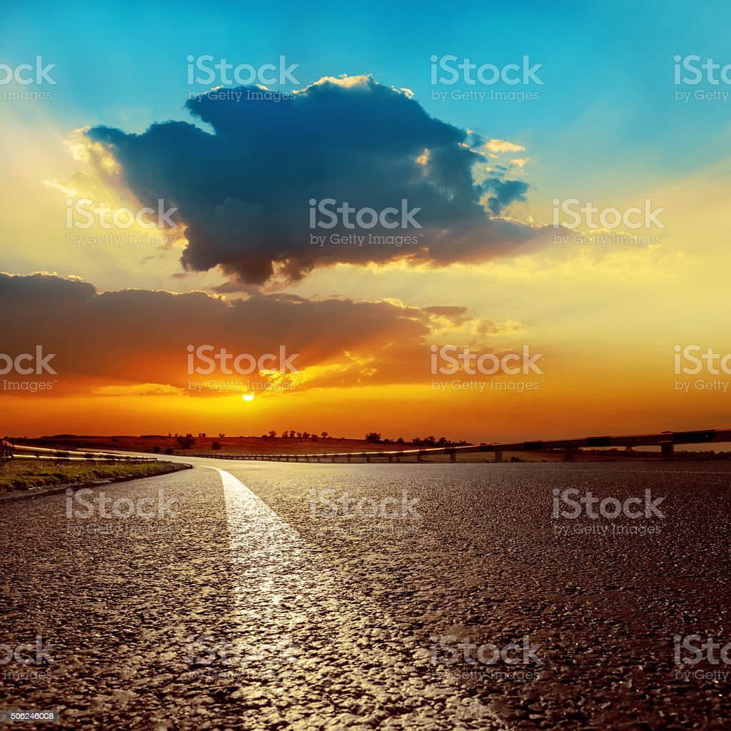 dramatic sunset over asphalt road closeup stock photo