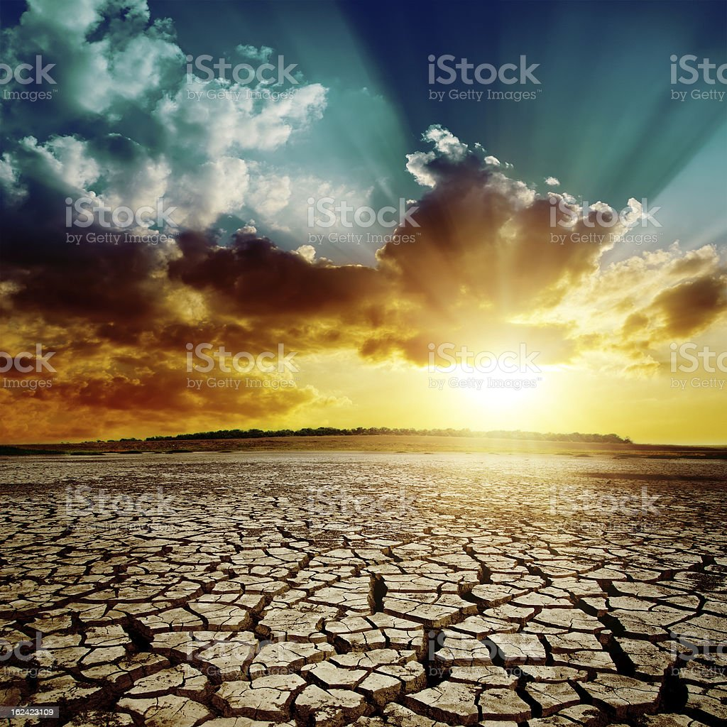 dramatic sunset over cracked earth stock photo
