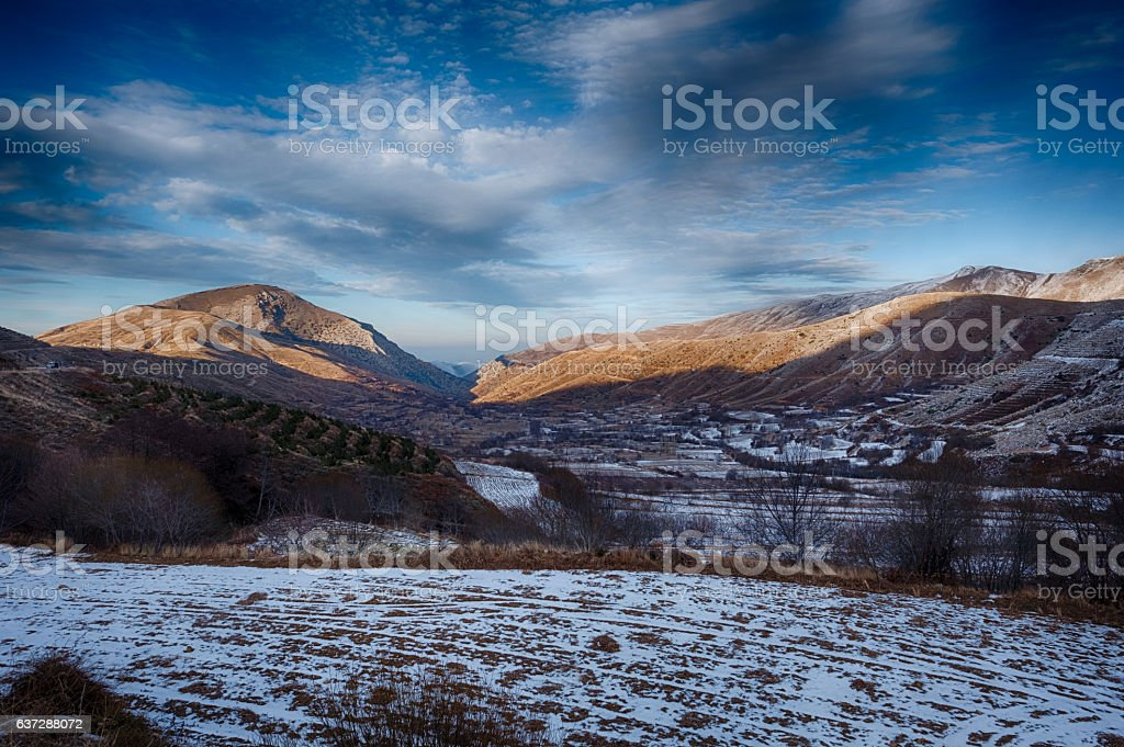 Dramatic sunset over icy fields and mountains stock photo