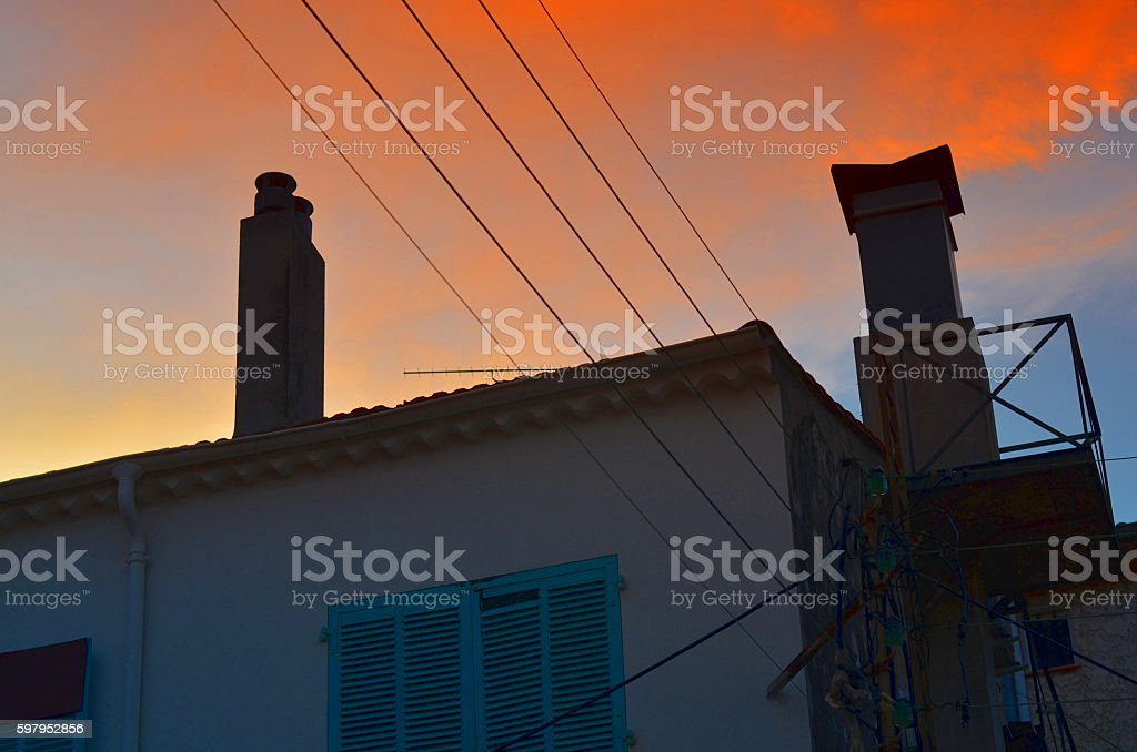 dramatic sunset over typical french roof with antenna stock photo