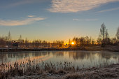 Dramatic winter landscape with frozen lake and sunrise.