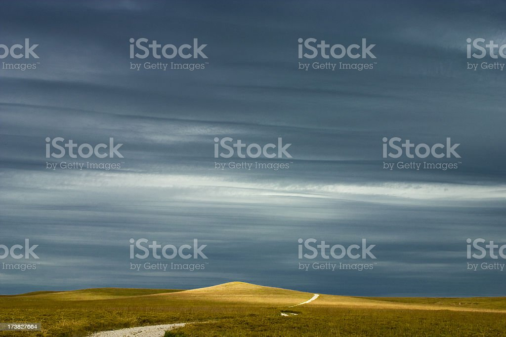 Dramatically lit Kansas praire landscape with isolated country road stock photo