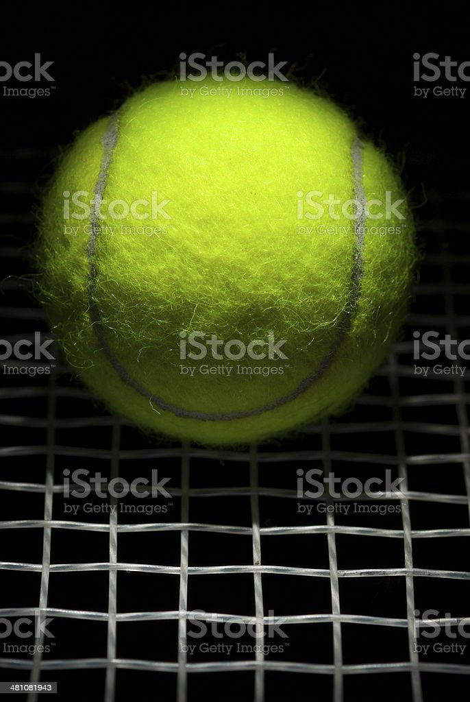 Dramatically Lit Tennis Ball on Strings stock photo