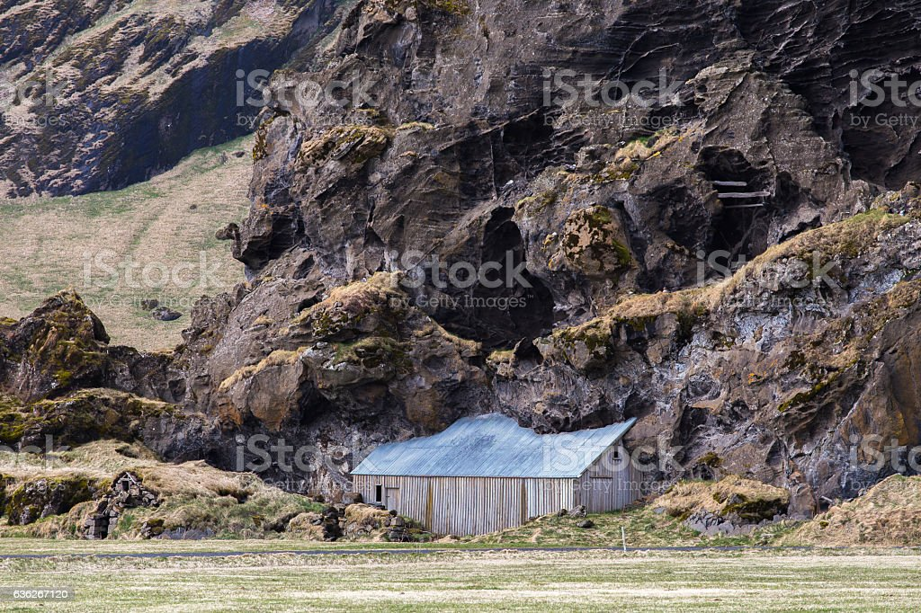 Drangshlid farm shed built into large rock Drangurinn, Iceland stock photo