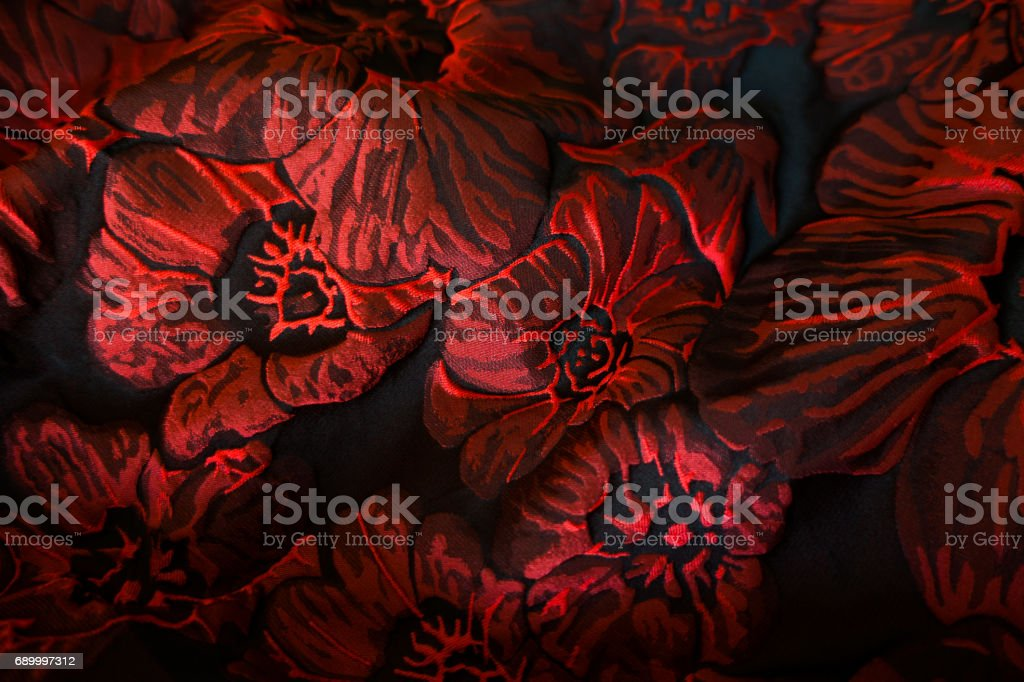 Draped matelasse jacquard fabric with floral pattern in red and black stock photo
