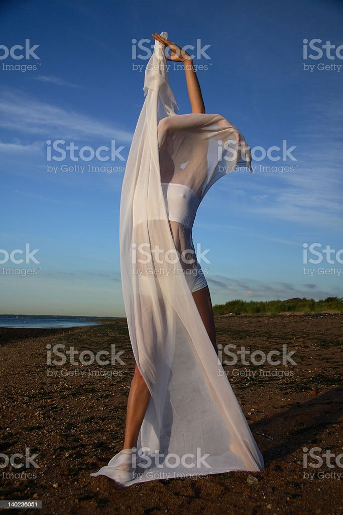 Draped Young Female Gymnast on a Beach, Artistically Posing stock photo