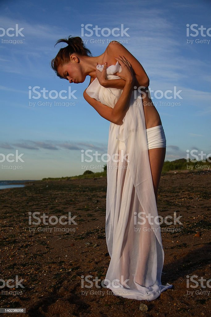 Draped Young Female Gymnast on a Beach, Bending Sideways royalty-free stock photo