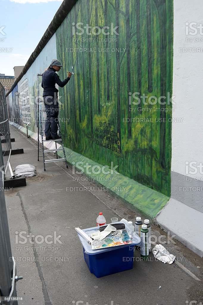Drawing a painting on the Berlin wall gallery stock photo