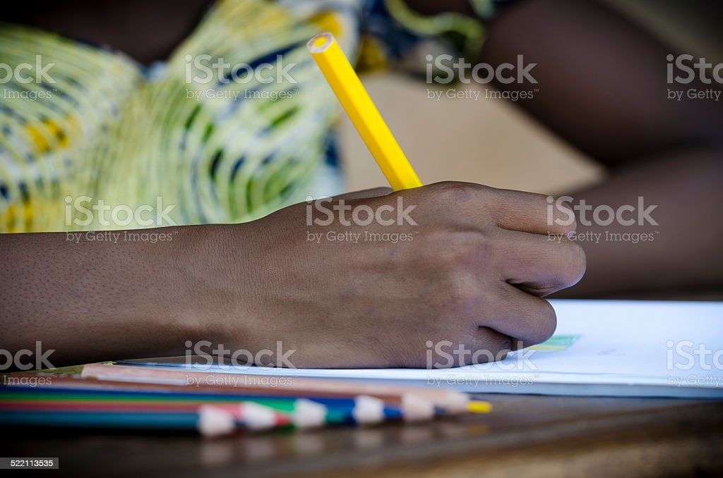 An African child is drawing with lots of colors in the public school...