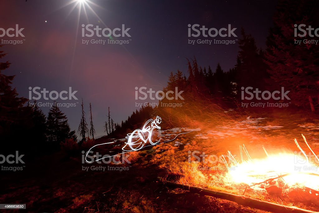 Drawing bicyclist with fire light in night stock photo