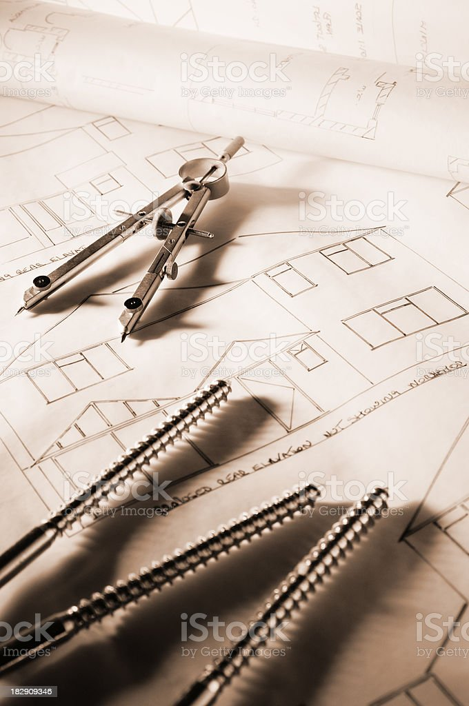 Drawing compass and bolts on house blueprints royalty-free stock photo
