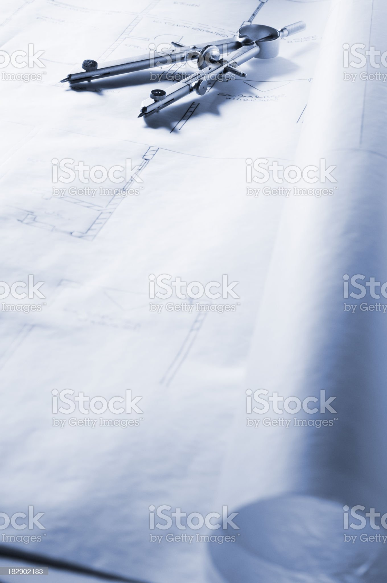 Drawing compass lying on blueprints of house royalty-free stock photo