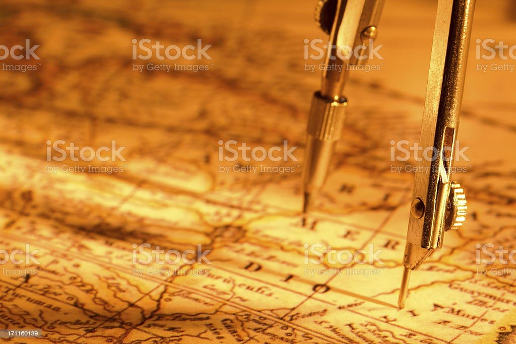 Drawing compass on antique world map royalty-free stock photo