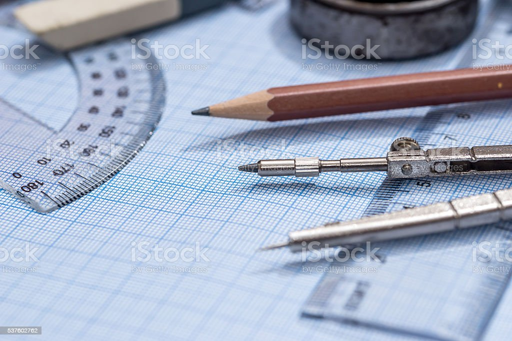 drawing compass, pencil, and ruler on graph paper background stock photo