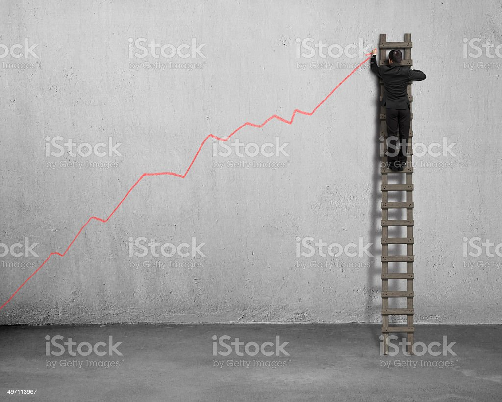Drawing growing red arrow on concrete wall stock photo