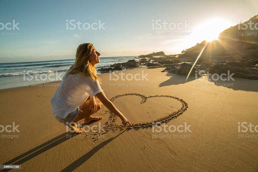 Drawing love on sandy beach stock photo