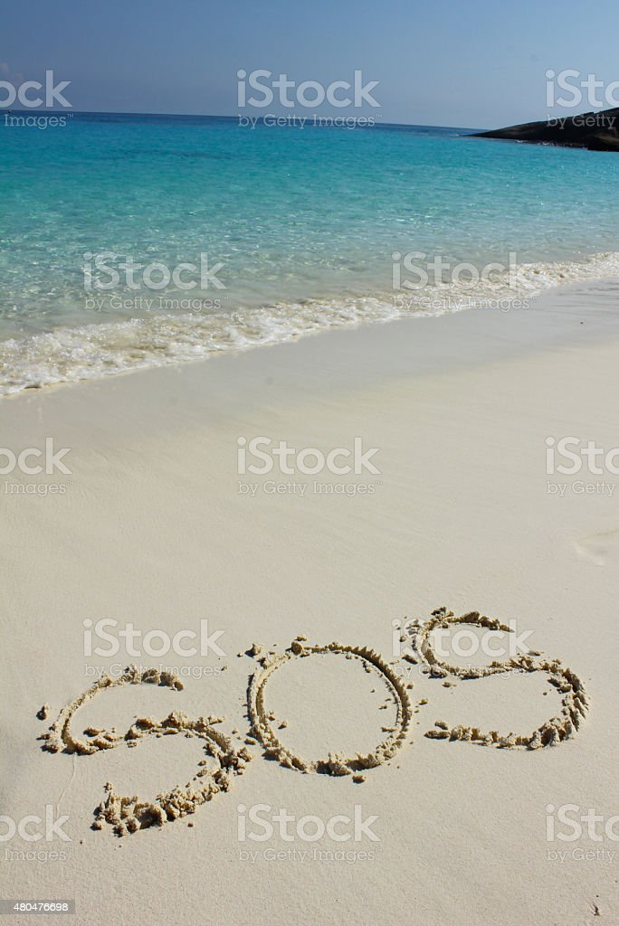 Drawing of 'SOS' on the beach sand at the sea stock photo