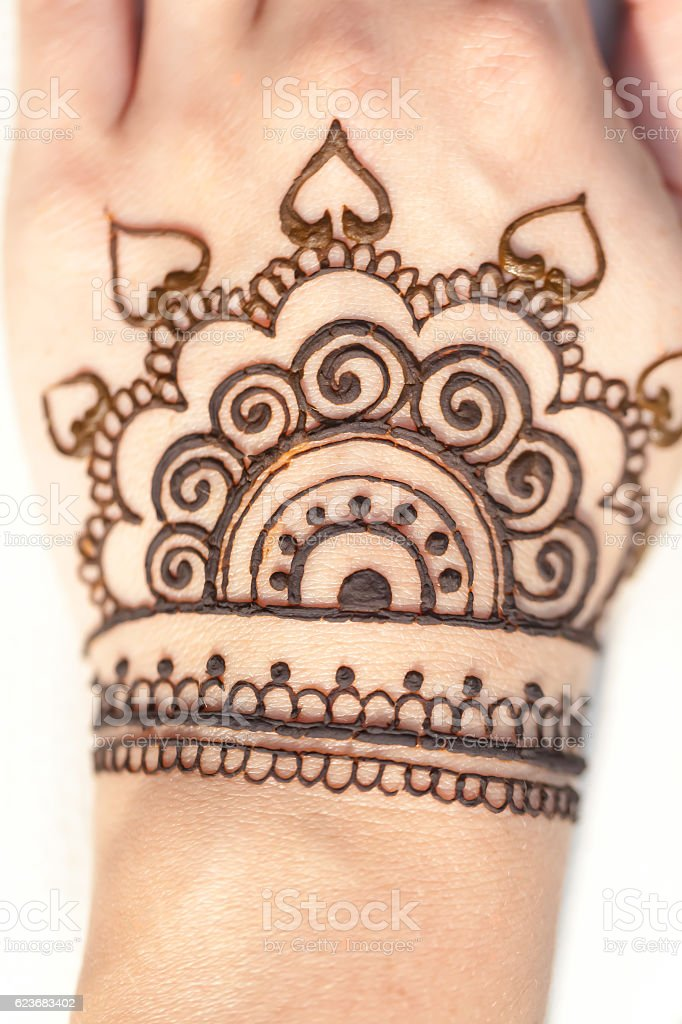 drawing pattern henna on a female hand stock photo