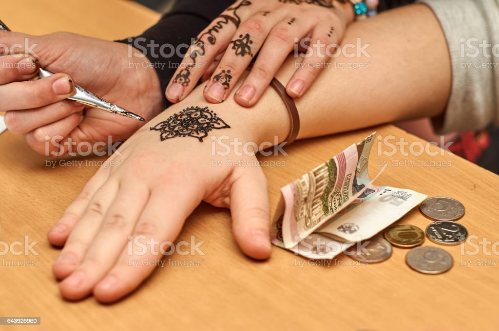 Drawing patterns by henna on the hands stock photo