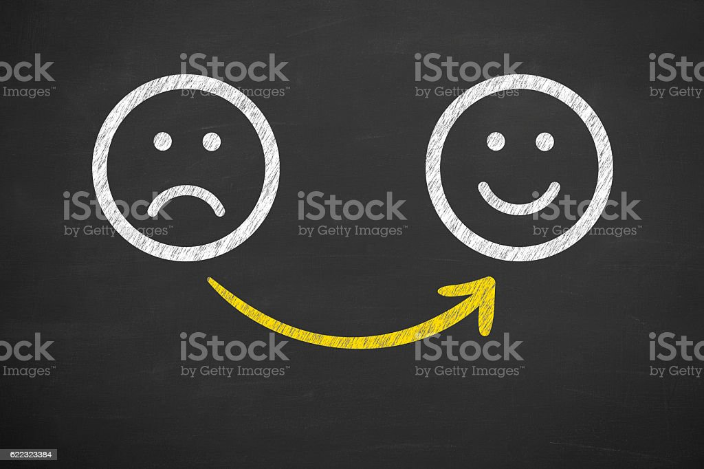 Drawing Unhappy and Happy Smileys on Chalkboard stock photo