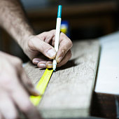 Drawing with construction pencil on wood and measuring tool