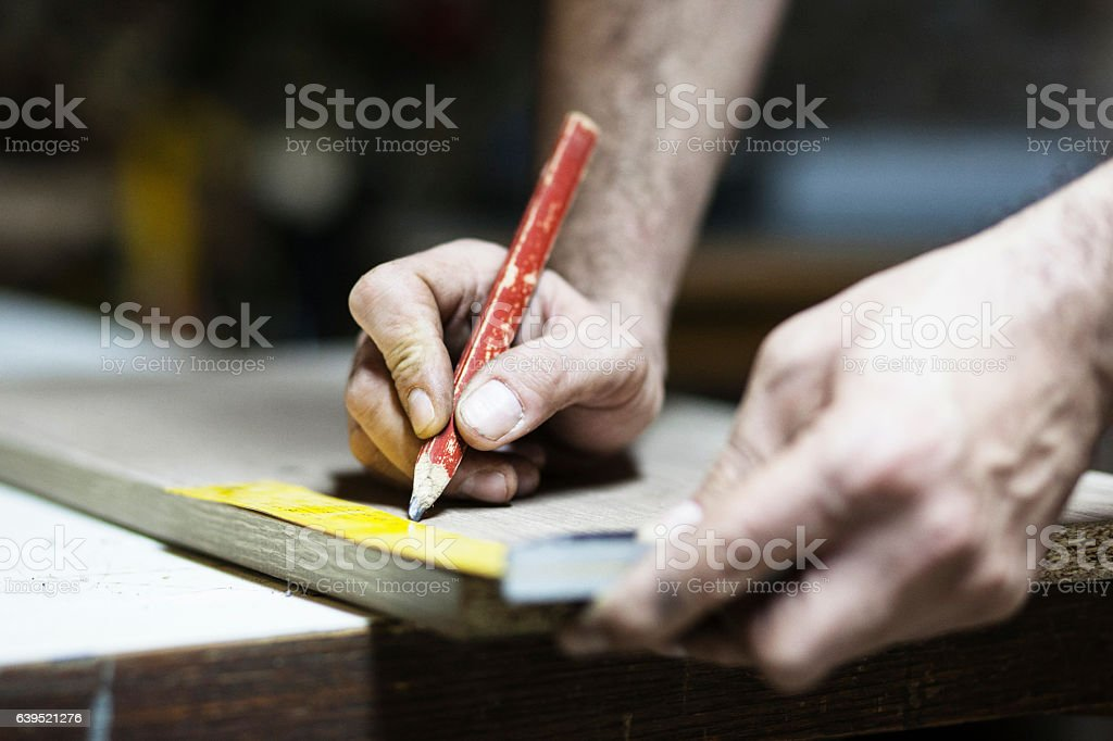 Drawing with construction pencil on wood and measuring tool stock photo