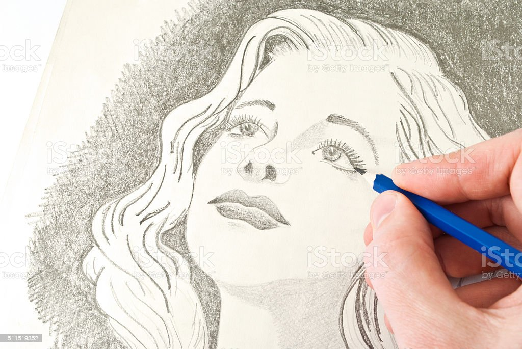 Drawing young blonde lady with a pencil stock photo