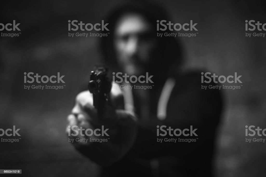 Dreaded brutal bandit holding his victim on gunpoint stock photo