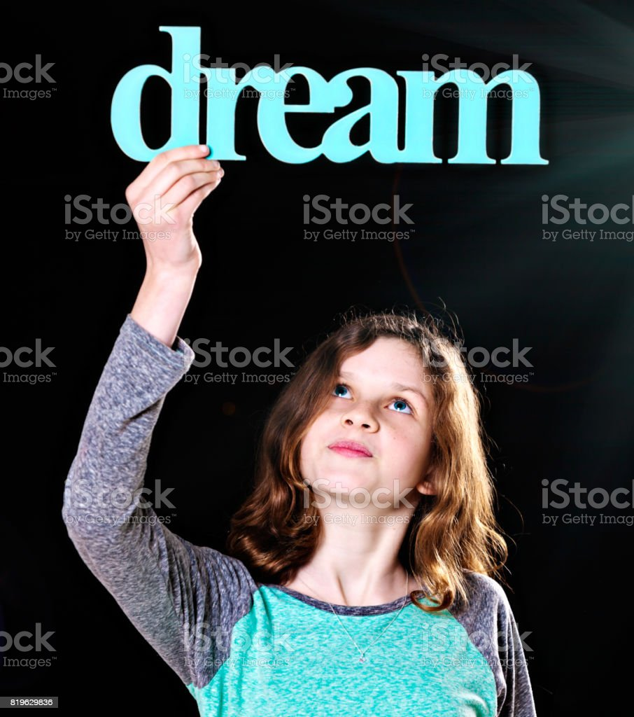 'dream' says sign held aloft by pretty pre-teen girl stock photo