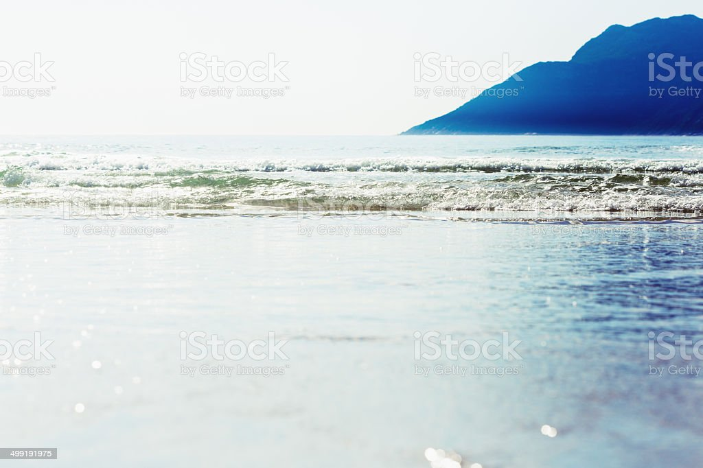 Dream vacation! Shoreline of idyllic beach with mountain background stock photo