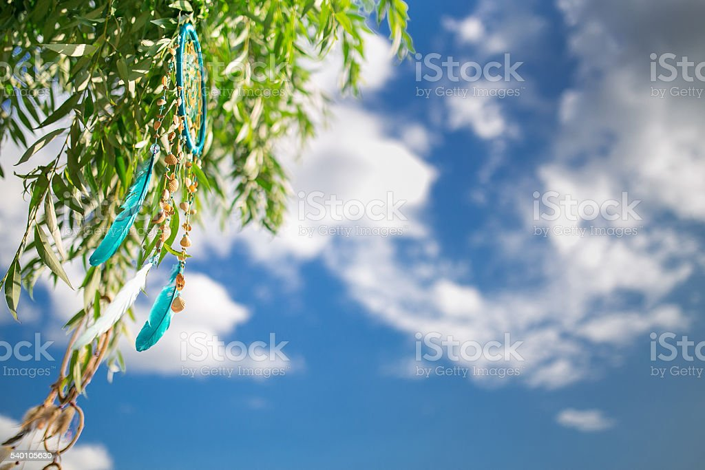 Dreamcatcher hangs on a tree on blue sky stock photo