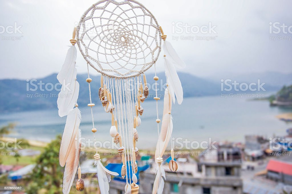 Dreamcatcher with a seashells on a mountain background. stock photo