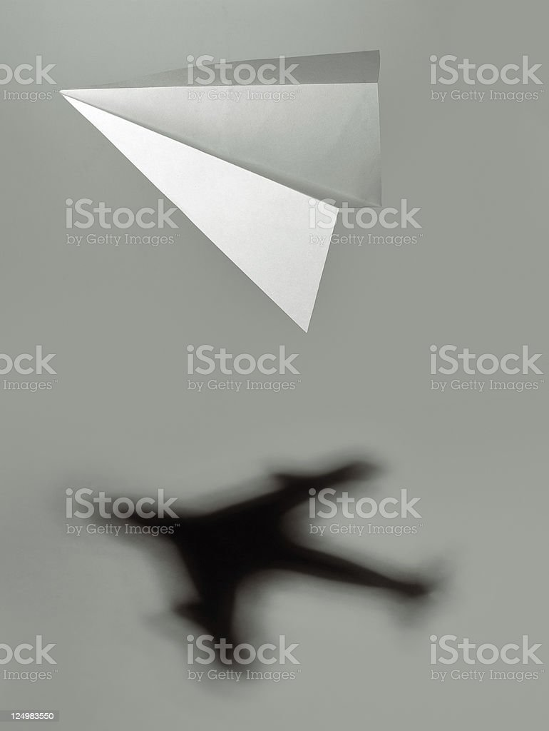 Dreaming big: paper plane casting an unreal jet airplane jet stock photo