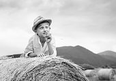 Dreaming boy lying on the rolling haystack