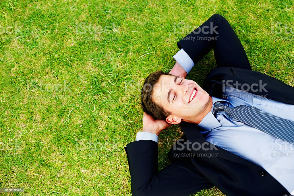 Dreaming - Business man resting on grass and smiling royalty-free stock photo