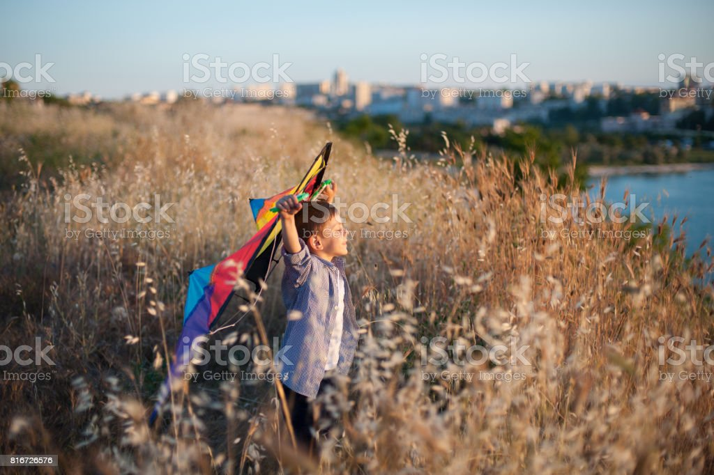 dreaming cute little boy with colorful kite on the field with sea and town on background stock photo