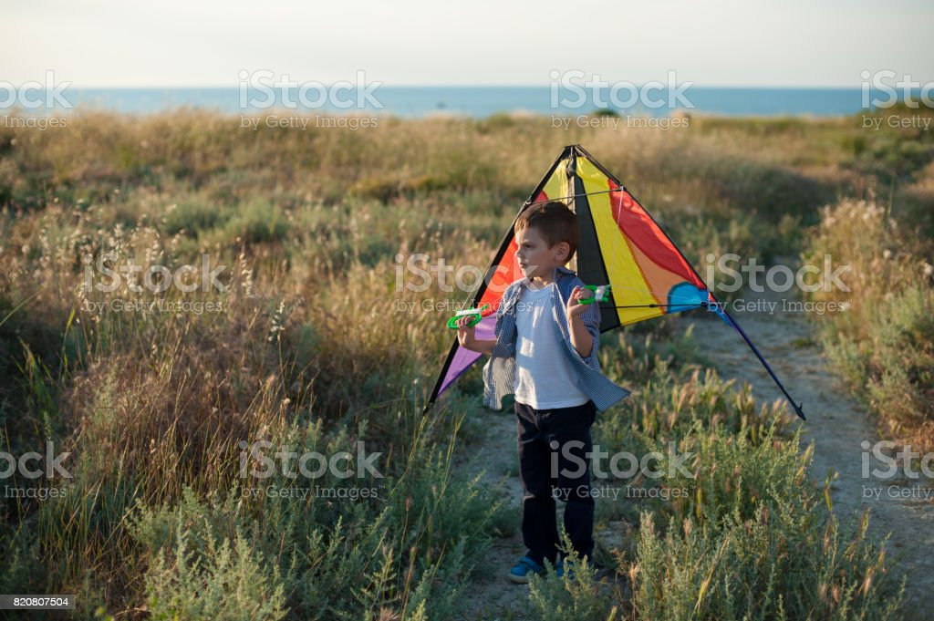 dreaming little boy holding a kite behind his shoulders stock photo