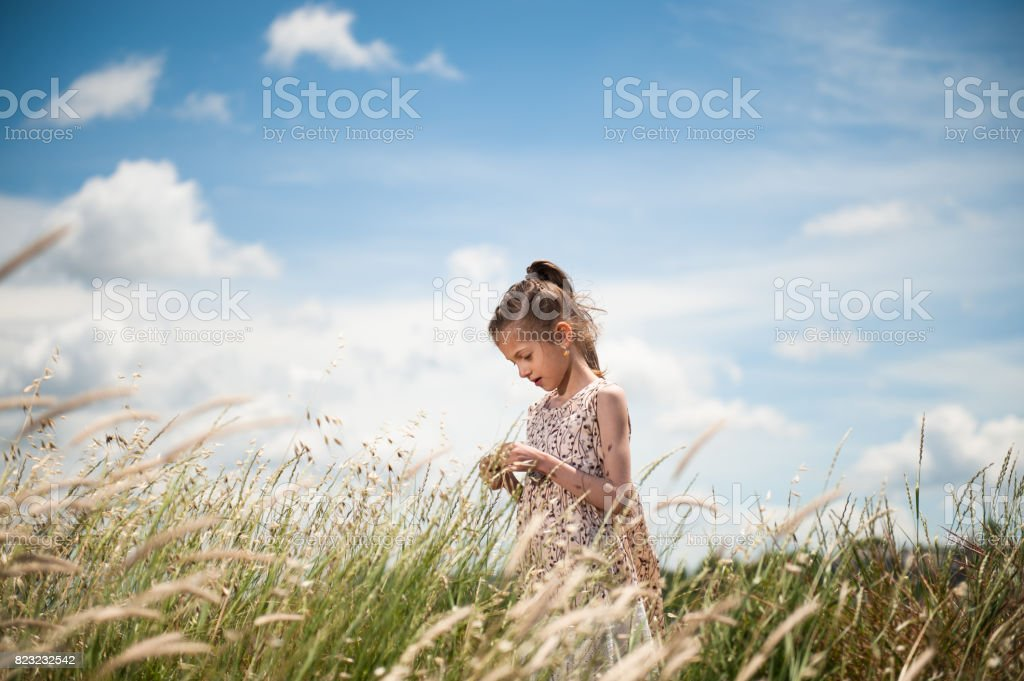 dreaming small girl wearing dress among the meadow on blue cloudy sky background stock photo