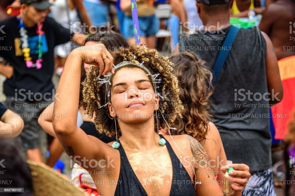 Dreaming woman with closed eyes, curly hair and fairy-lights on her head, sprinkling golden glitter on herself at Carnaval 2017 stock photo