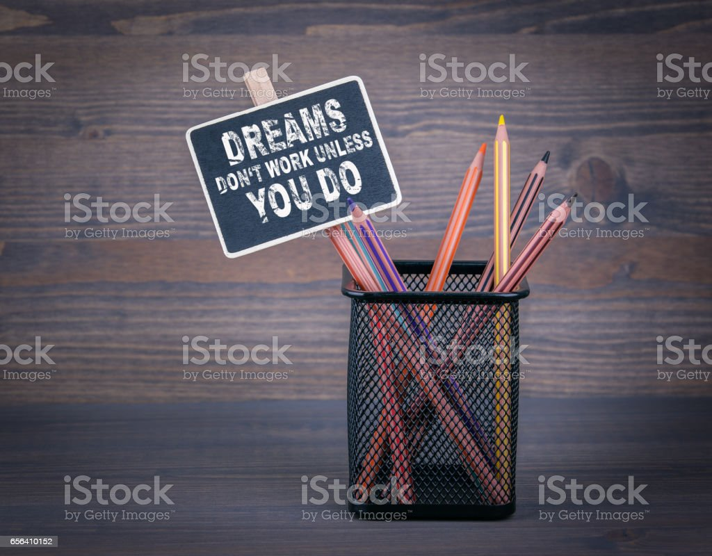 Dreams don't work unless you do. A small blackboard chalk and colored pencil on wood background stock photo