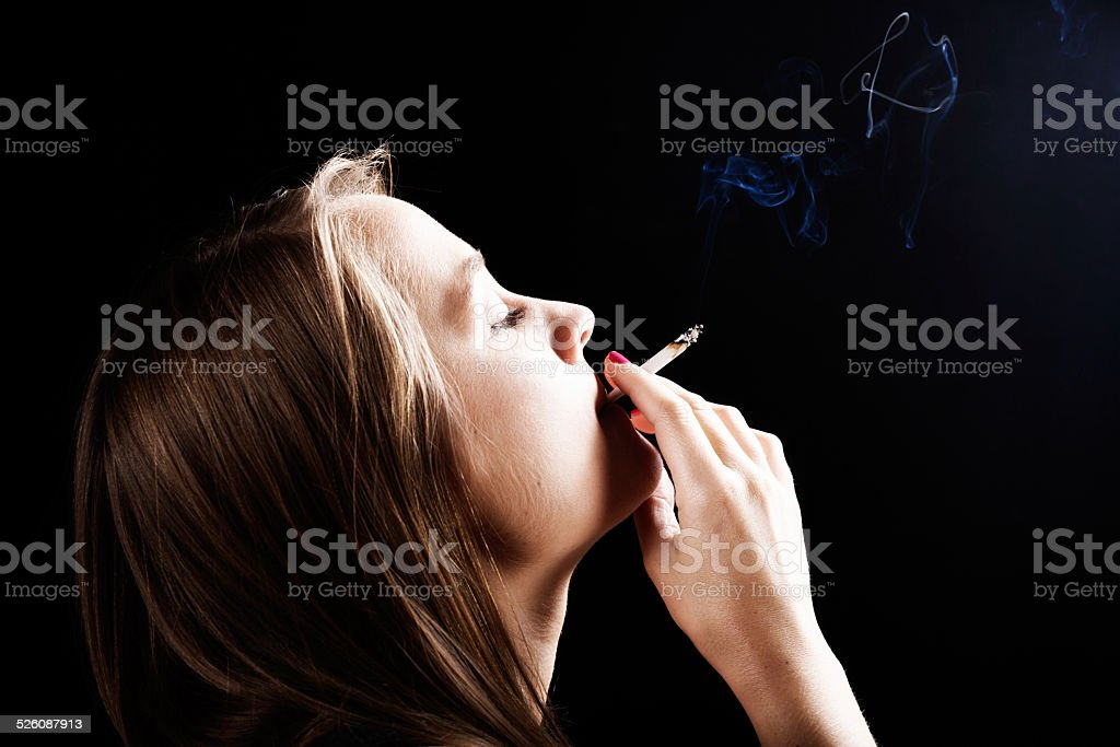 Dreamy blonde puffing on joint of marijuana stock photo