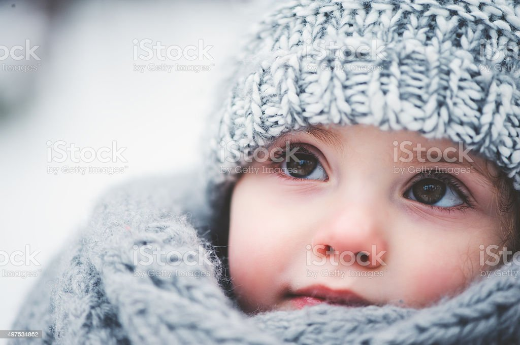 dreamy cozy outdoor portrait of toddler child girl in winter stock photo