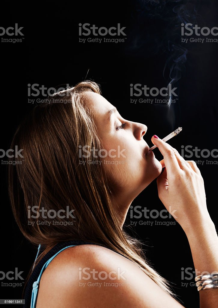 Dreamy druggie! Profile of young woman smoking a reefer stock photo