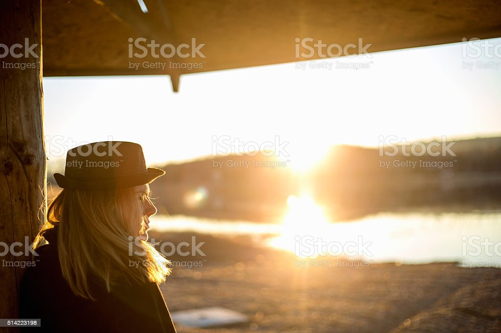 Dreamy girl accompanies a beautiful sunset near the river stock photo