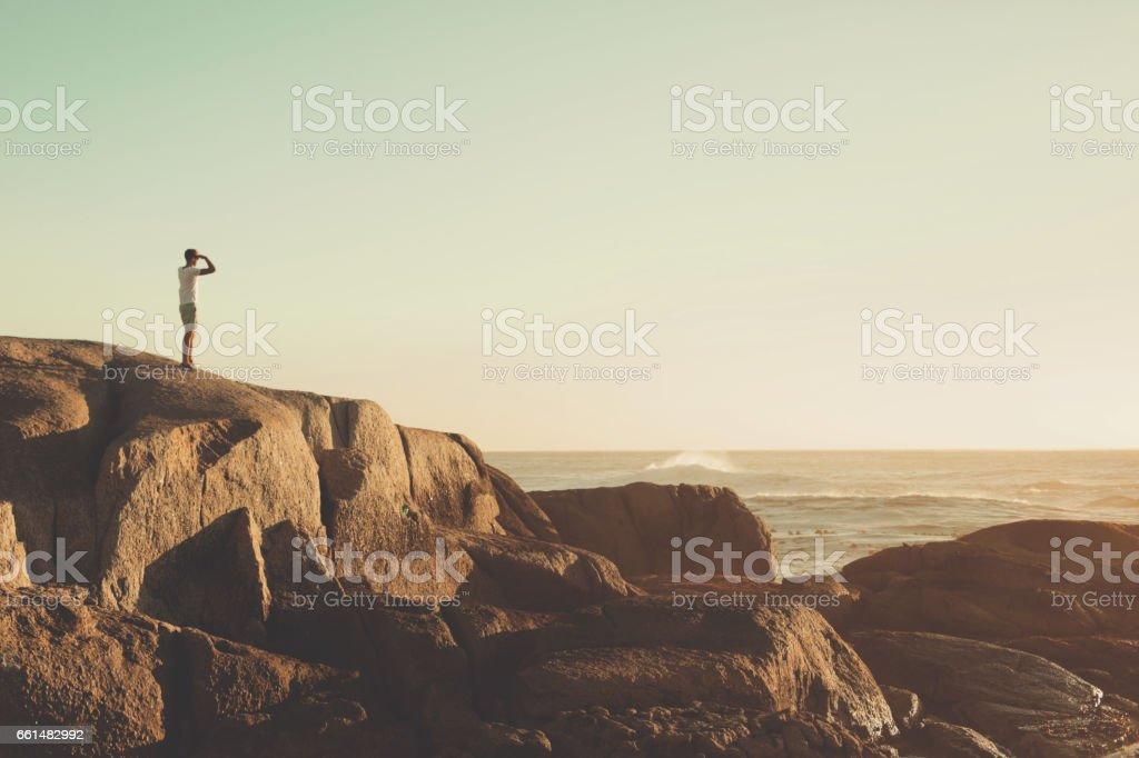 Dreamy man gazing at sun set on the edge of the sea stock photo
