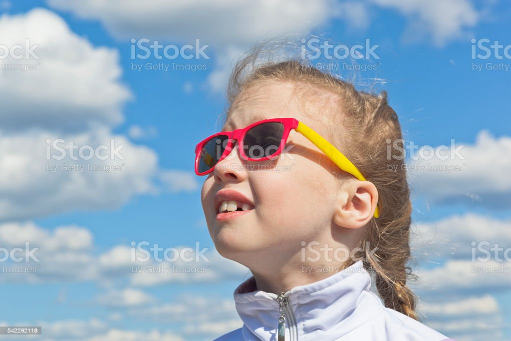 Dreamy small girl against the sky with clouds stock photo