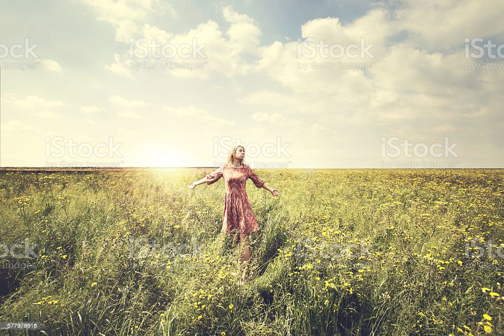 dreamy woman walking in nature illuminated by the sun stock photo