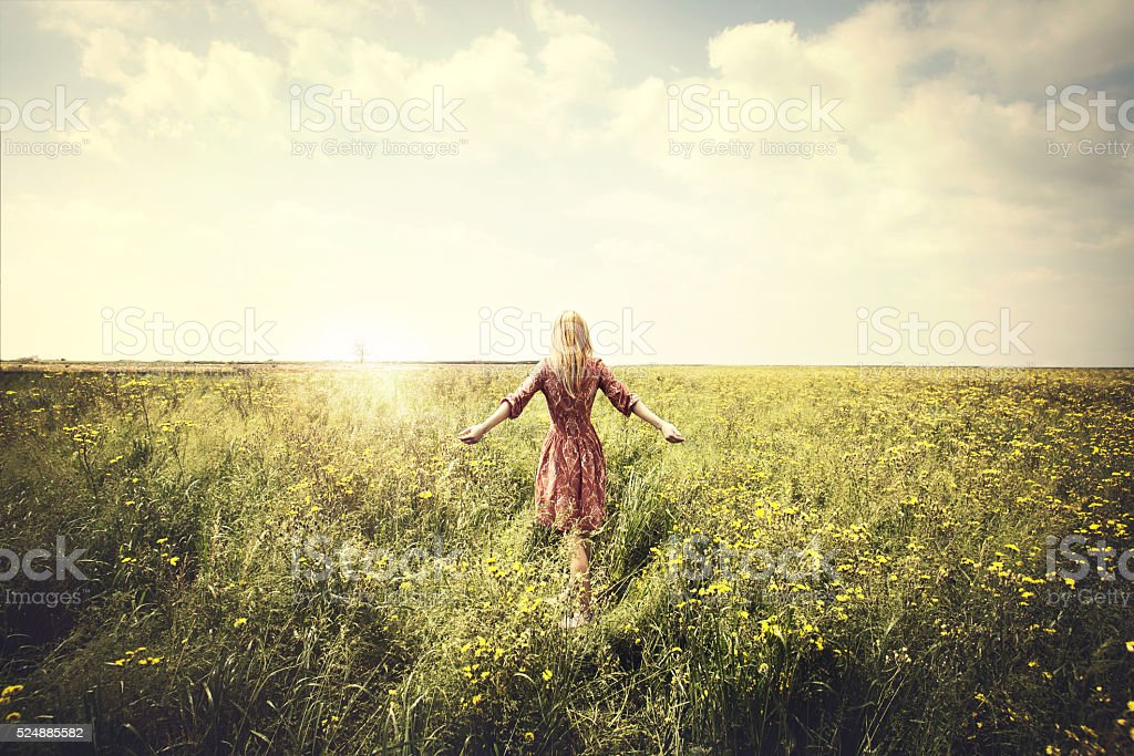 dreamy woman walking in nature towards the sun stock photo