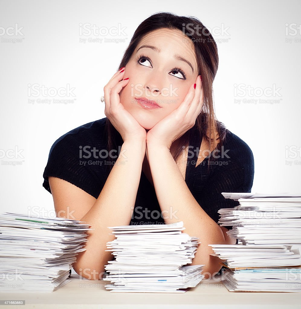 Dreamy Young Woman Preoccupied with Unpaid Bills and Paperwork Overload stock photo
