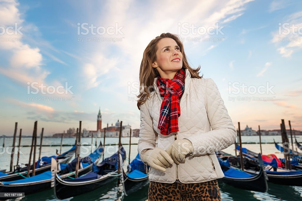 Dreamy young woman traveler standing on embankment in Venice stock photo
